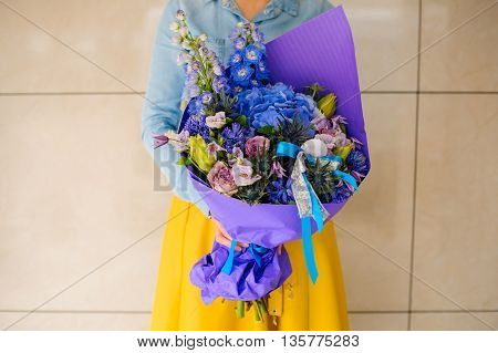 girl holding purple and pink flower bouquet no face