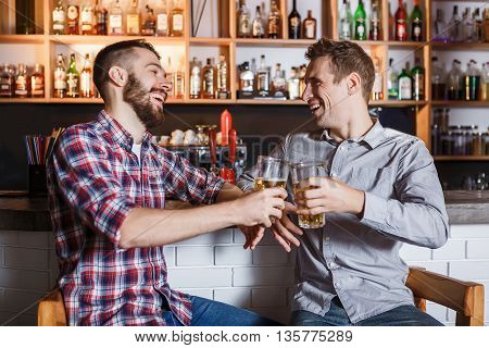 Happy smiling friends drinking beer at counter in pub