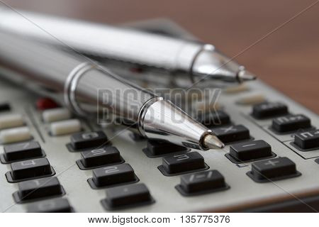 Business background with table pens and calculator.