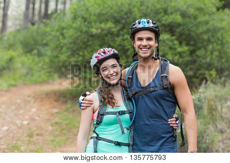 Portrait of happy bikers standing on field in forest