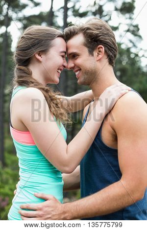 Smiling happy young couple standing against trees in forest