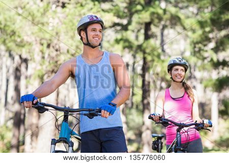 Healthy man and woman with bicycles looking away in forest