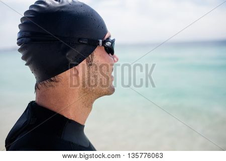 Young man in wetsuit and swimming goggles standing on beach on a sunny day