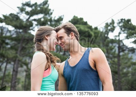 Low angle view of young couple couple standing against trees at forest
