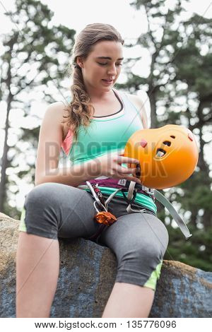 Low angle view of young woman sitting on rock against trees at forest