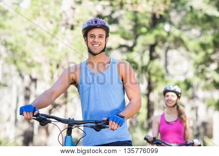 Portrait of smiling young man with woman riding bicycle in forest