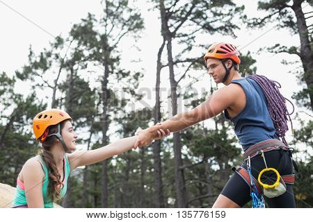 Young couple holding hands against trees at forest