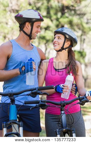 Happy couple holding water bottles while riding bicycle at forest