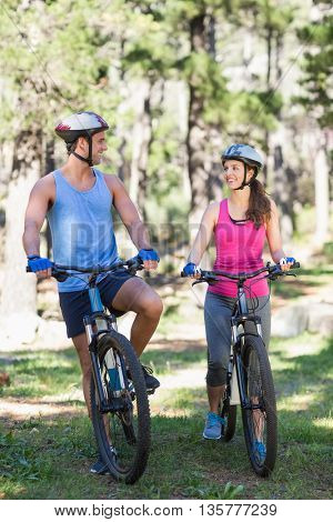 Smiling young couple riding bicycle against trees at forest