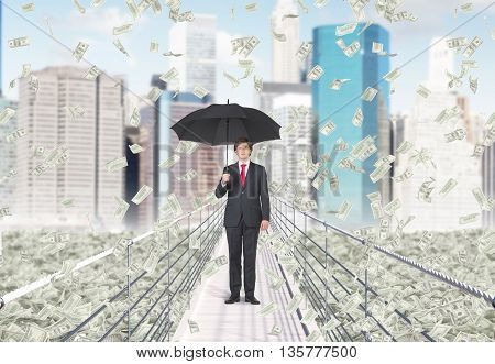 Financial growth and success concept with businessman holding umbrella and standing in the middle of bridge with abstract dollar banknote rain on New York city background
