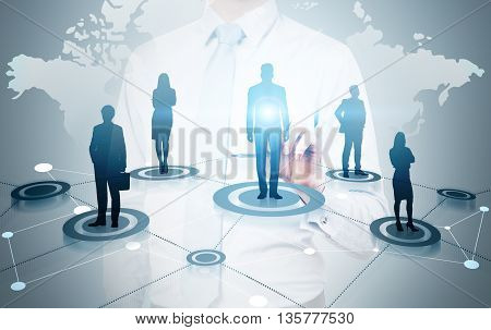 Global social networking concept with businessman pointing at map abstract network and businesspeople silhouettes on light grey background