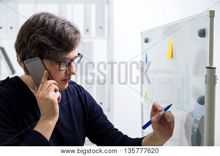 Concentrated young man in glasses talking on the phone and drawing business charts on office whiteboard