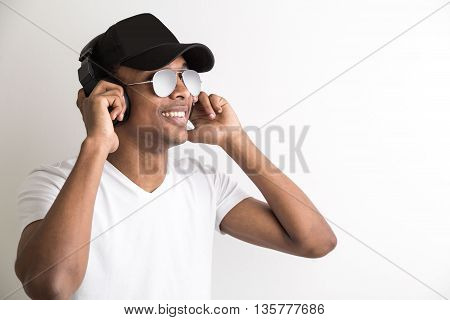Portrait of smiling african american guy in cap and glasses listening to music with headphones on light background