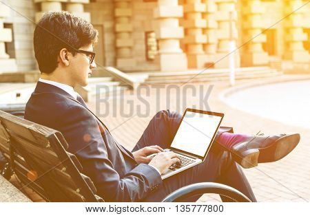 Side view of young businessman sitting on bench using laptop with blank screen outside on beautiful building background. Toned image Mock up