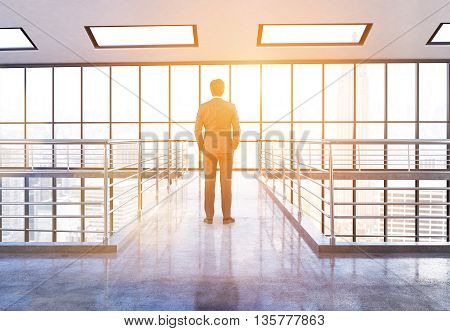 Thoughtful businessman standing in office interior with railings New York city view and sunlight. 3D Rendering