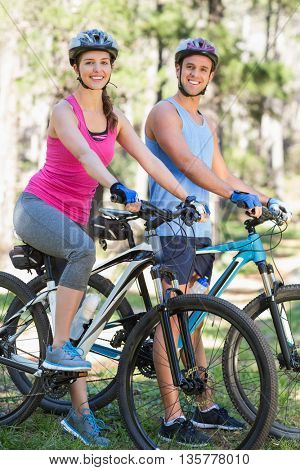 Portrait of smiling young couple riding bicycle at forest