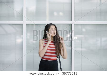 Young Asian woman talking on smartphone near glass wall of office building. Young woman on city background.