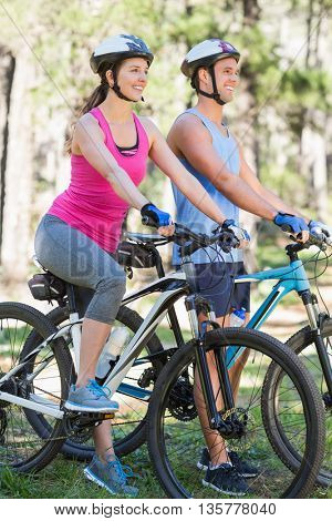 Smiling young couple riding bicycle at forest