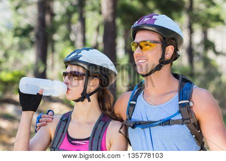 Woman wearing helmet with man drinking water against trees at forest