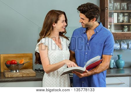 Young couple reading recipe book together in kitchen at home