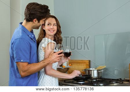 Young couple holding wine glass in kitchen at home