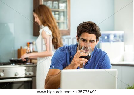 Man having red wine and using laptop in kitchen while woman cooking food in background