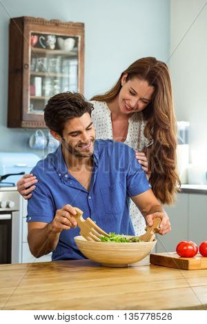 Young happy couple mixing a salad in kitchen at home
