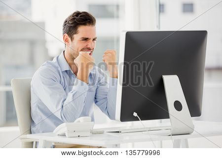 Businessman cheering in his office at his desk