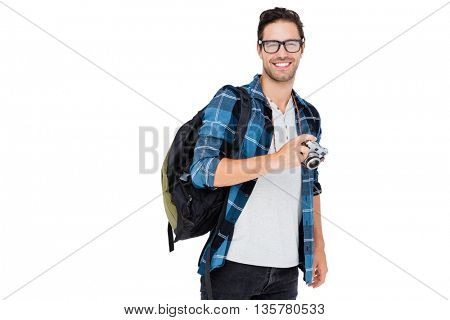 Portrait of young man carrying rucksack and holding camera on white background