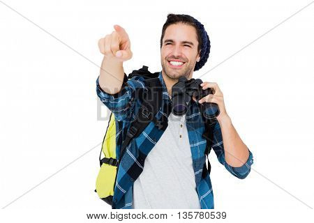 Young man carrying rucksack and using camera on white background