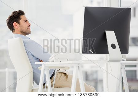 Relaxed businessman sitting with arms crossed in the office