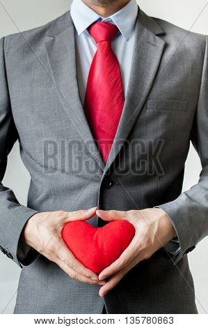 Businessman Showing Compassion Holding Red Heart In His Suit - Crm, Service Mind Business Concept