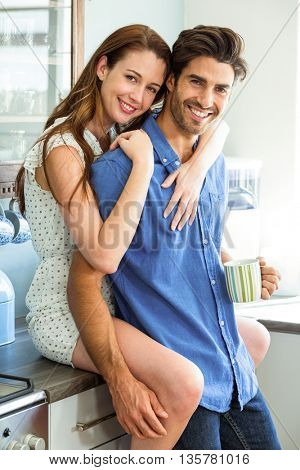 Portrait of young couple embracing in kitchen while having coffee at home