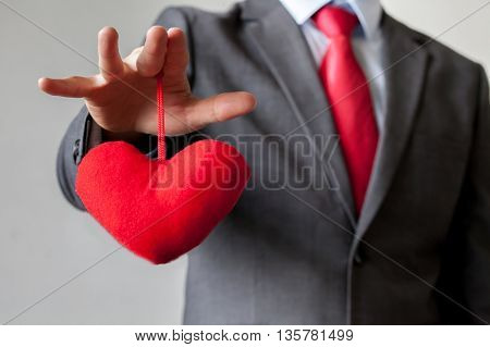Businessman Winning And Controling Customer's Heart Concept