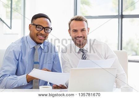 Portrait of businessmen sitting and holding a report in office