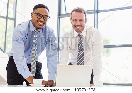 Portrait of businessmen using laptop at desk in office