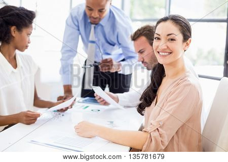 Business people discussing a report at meeting in office