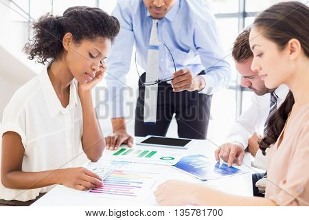 Business people looking at reports in meeting in office
