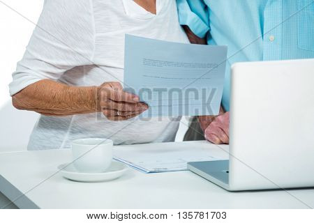 Midsection of senior woman with man holding document at home
