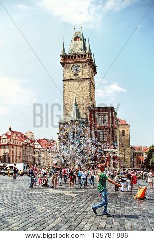 PRAGUE, CZECH REPUBLIC - JUNE 06 2016: Unidentified young man makes soap bubbles in Old Town Square (Staromestske namesti) in Prague Czech Republic.