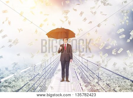 Financial growth and success concept with businessman holding umbrella and standing in the middle of bridge with abstract dollar banknote rain on cloudy background with sunlight