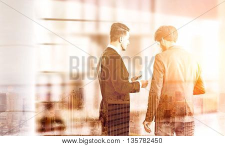 Two businesspeople discussing business contract on New York city background. Double exposure