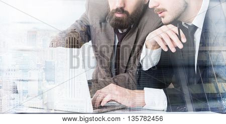 Closeup of two businessmen sitting at office desk discussing project on laptop. Concept of teamwork. New York city background. Double exposure