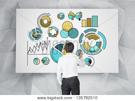 Young businessman drawing business pie charts on whiteboard hanging on abstract polygon patterned wall