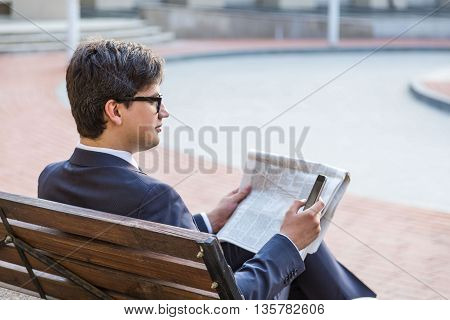 Young attractive businessman sitting on outdoor bench holding news paper and using smart phone