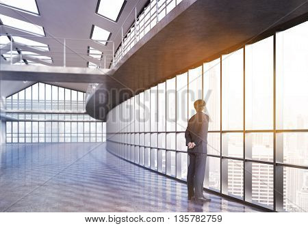 Businessman looking out the window in empty office interior with railings and New York city view. 3D Rendering