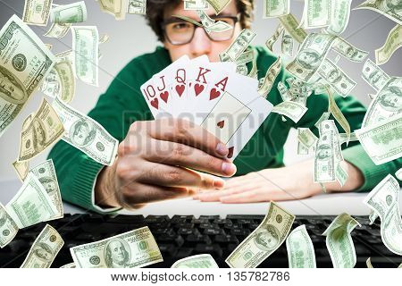 Young man holding royal flash poker cards with keyboard on table and abstract dollar bill rain. Gambling concept