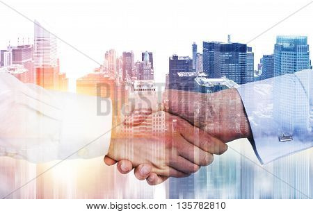 Closeup of handshake on New York city background with sunlight. Double exposure