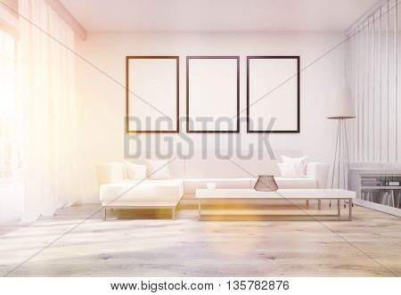 Front view of living room interior with three blank picture frames white couch coffee table floor lamp bookshelf and window with city view. Toned image. Mock up 3D Rendering
