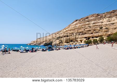 CRETE GREECE-JULY 22: Tourists on Matala beach with the caves on Libyan sea on July 222014 Crete island Greece.